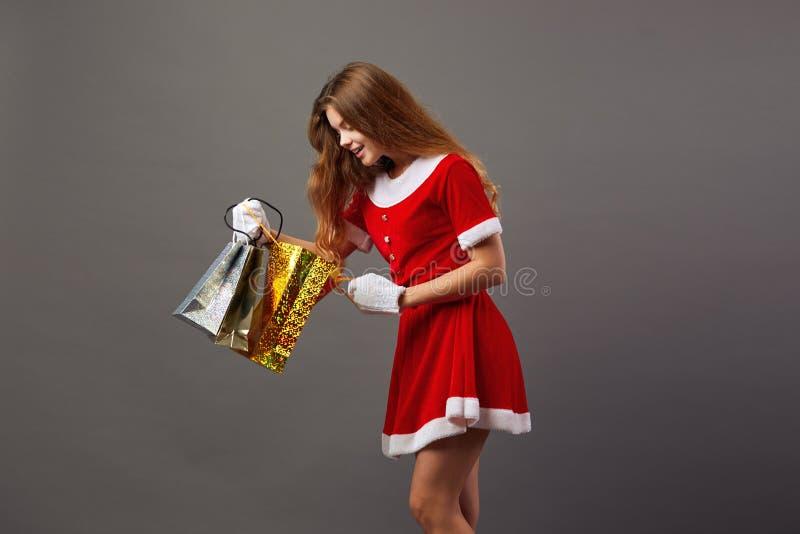 Jeune et belle Mme Santa Claus dans des lunettes de soleil habillées dans la robe longue rouge et les gants blancs tient les sacs photo libre de droits