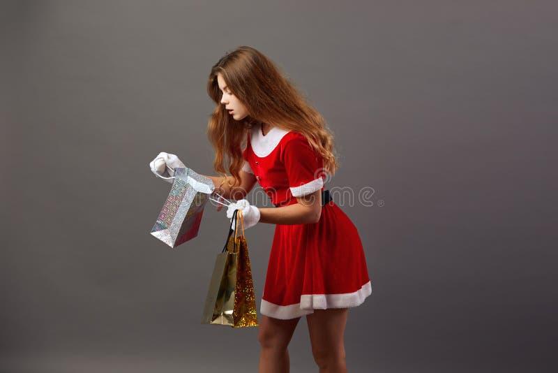 Jeune et belle Mme Santa Claus dans des lunettes de soleil habillées dans la robe longue rouge et les gants blancs tient les sacs image libre de droits