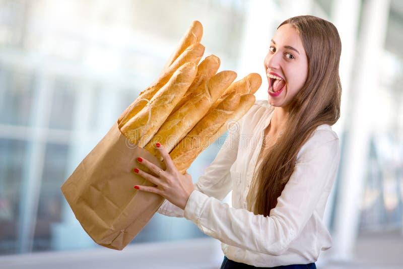 Jeune et drôle femme mangeant des baguettes devant le magasin de boulangerie images libres de droits