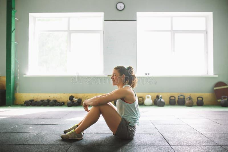 Jeune et forte fille avec un sourire faisant des exercices pour les muscles de l'estomac, presse sur le plancher dans la spore images libres de droits