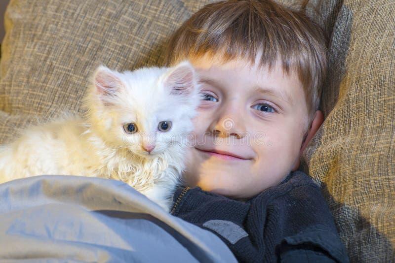 Jeune et gai garçon avec un chat blanc sur le divan observant l'appareil-photo image stock