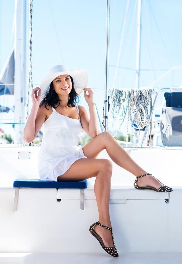 Jeune et heureuse femme détendant sur un bateau images stock