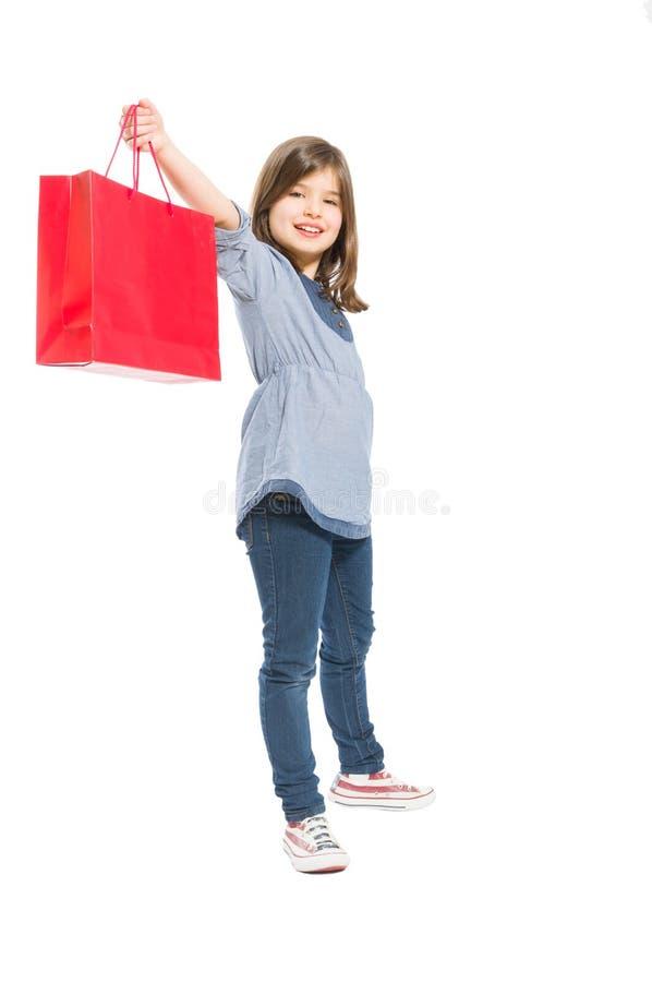Jeune et mignonne fille d'achats tenant un sac rouge photo libre de droits
