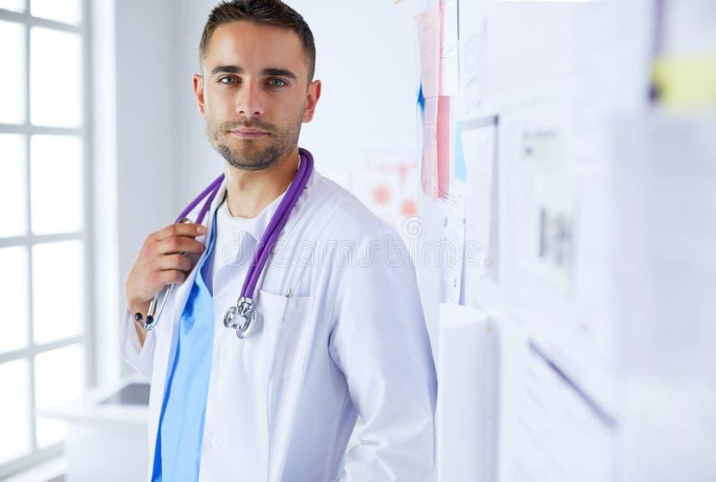 Jeune et sûr portrait masculin de docteur se tenant dans le bureau médical photographie stock