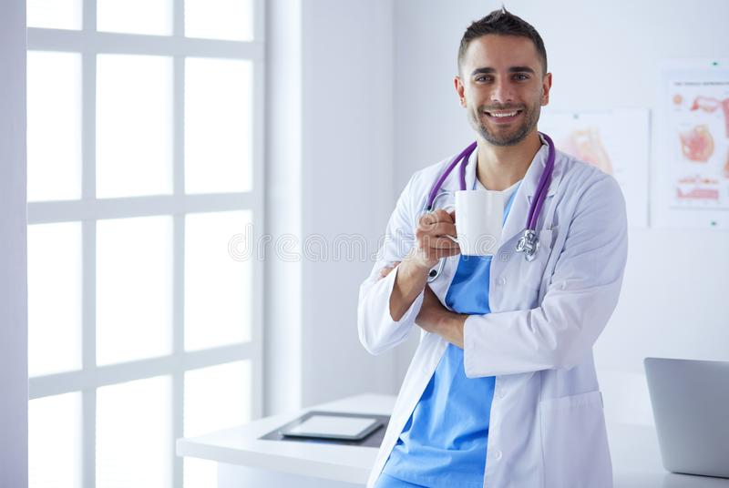 Jeune et s?r portrait masculin de docteur se tenant dans le bureau m?dical images stock