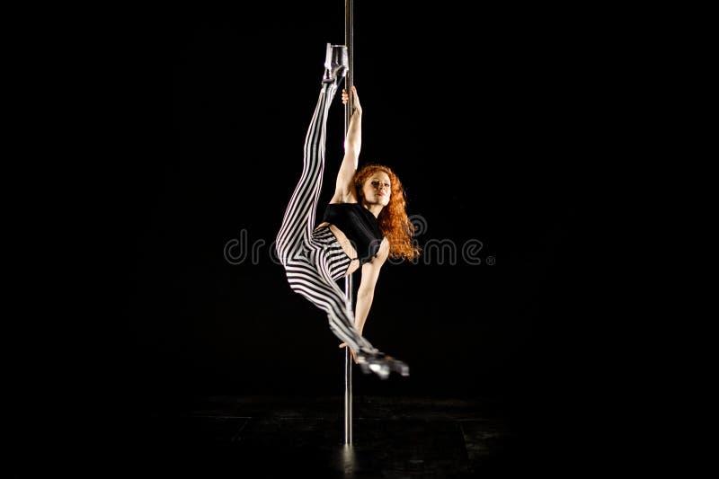 Jeune et sexy danse de poteau d'exercices de femme sur le fond foncé images stock