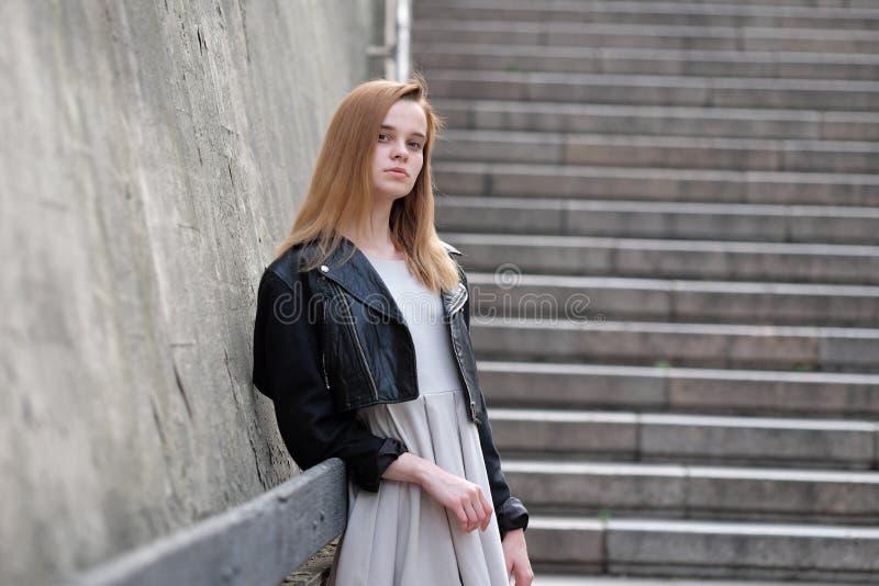 Jeune et sexy fille de roux posant dehors dans la veste en cuir et la robe photographie stock libre de droits