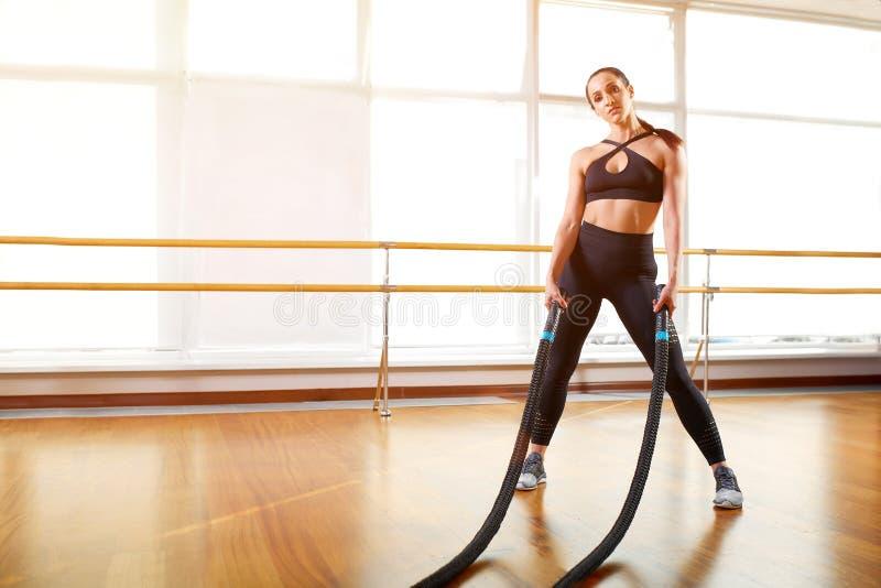 Jeune et sportive fille attirante employant les cordes s'exerçantes dans le gymnase Sport de concept, séance d'entraînement, la v photo libre de droits