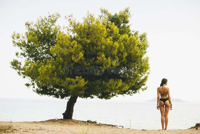 Jeune et sportive fille posant sur une plage images stock