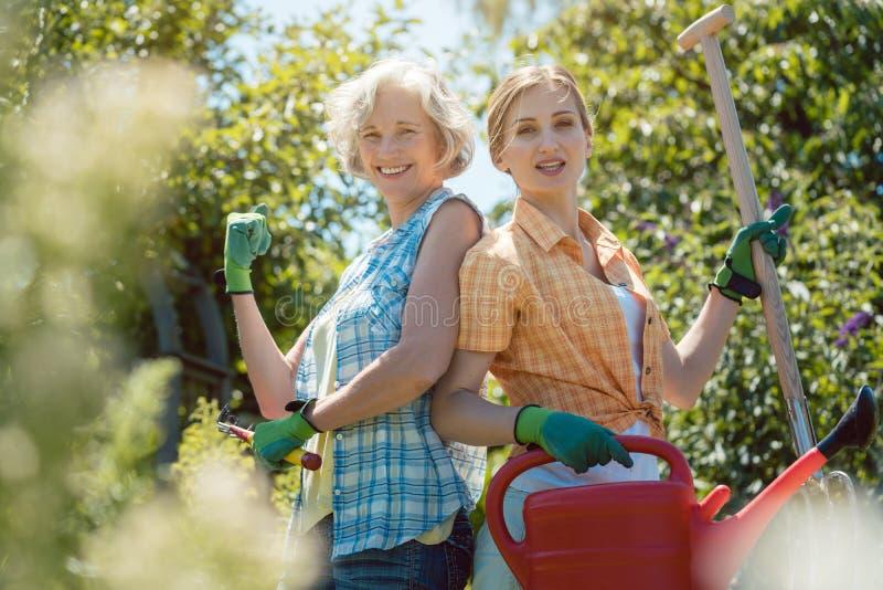 Jeune et supérieure femme posant pour la photo dans leur jardin photos stock