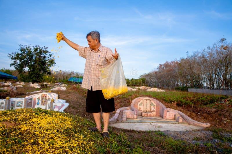 Jeune et vieux priez avant les ancêtres, balayent les tombes au photos libres de droits