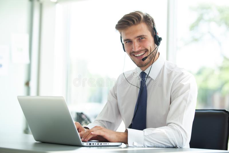 Jeune exécutif masculin heureux de support à la clientèle fonctionnant dans le bureau photos libres de droits