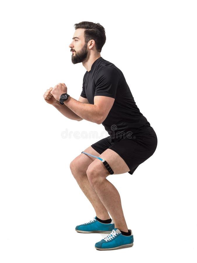 Jeune exercice d'accroupissement d'athlète avec la bande de résistance autour des jambes photos libres de droits