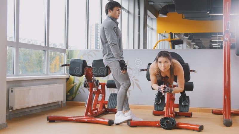 Jeune exercice de femme de forme physique abdominal dans le gymnase - homme musculaire regardant à elle image stock