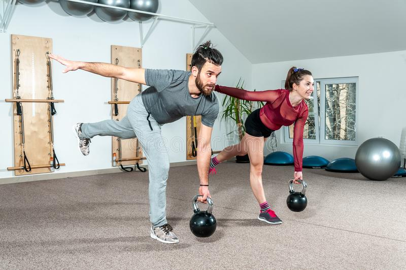 Jeune exercice de forme physique de kettlebell de séance d'entraînement de couples dans le gymnase, foyer sélectif images libres de droits