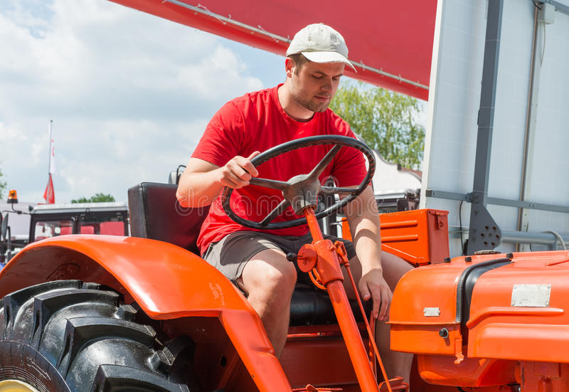 Jeune exploitant agricole dans le tracteur photo libre de droits