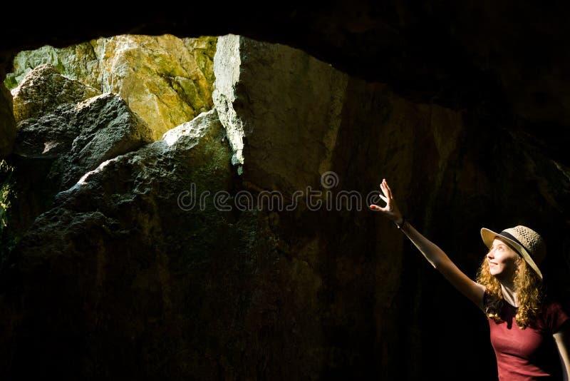 Jeune explorateur une fille au pointage de chapeau et trou dans la caverne antique photo stock