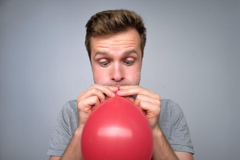 Jeune explosion européenne d'homme un ballon rouge photos libres de droits