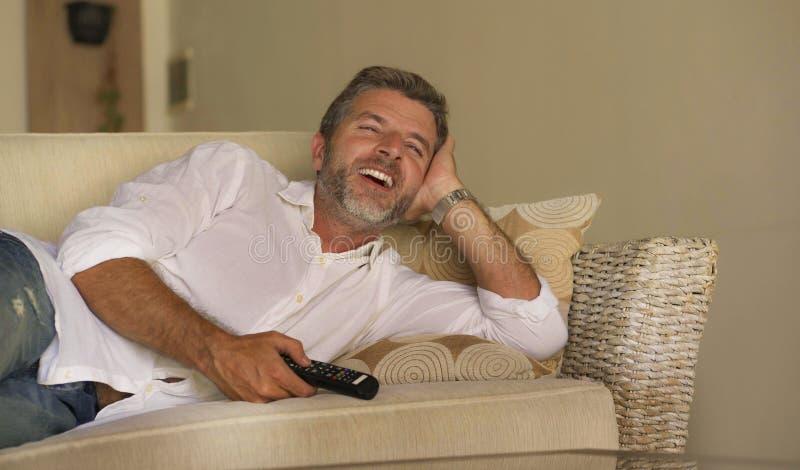Jeune exposition attrayante de télévision d'homme heureux et gai ou film drôle de observation de comédie riant l'extérieur décont images stock