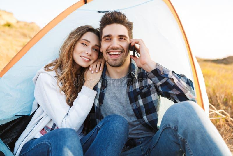 Jeune extérieur affectueux heureux de couples dans le camping alternatif libre de vacances parlant par le téléphone portable images libres de droits
