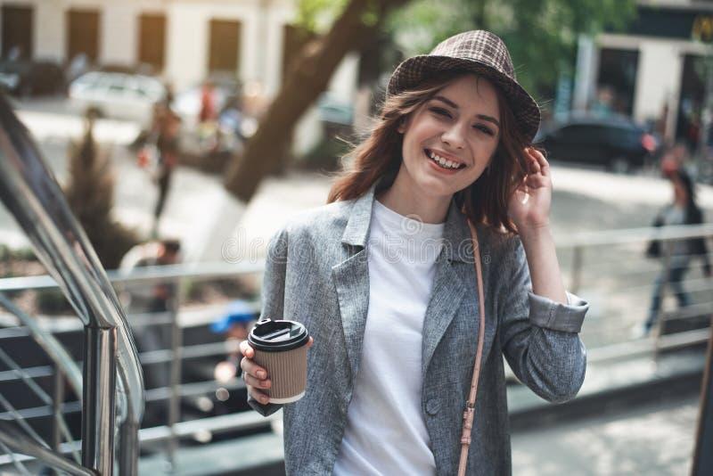 Jeune extérieur debout de sourire de dame avec la boisson chaude photographie stock libre de droits