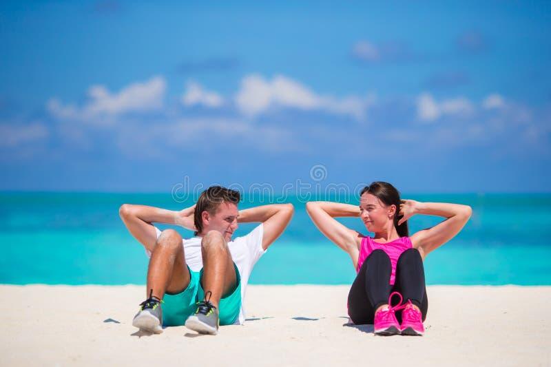 Jeune faire de couples de forme physique se reposent se lève sur la plage blanche image libre de droits