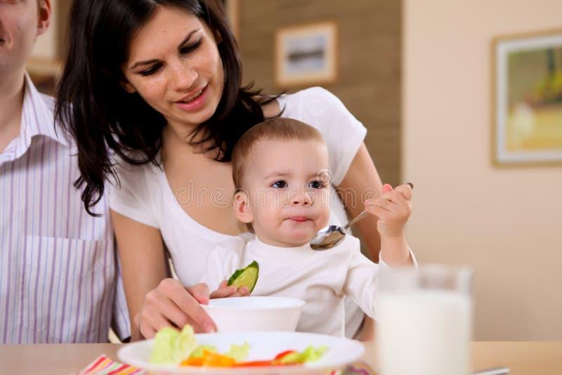 Jeune famille à la maison ayant le repas photographie stock libre de droits