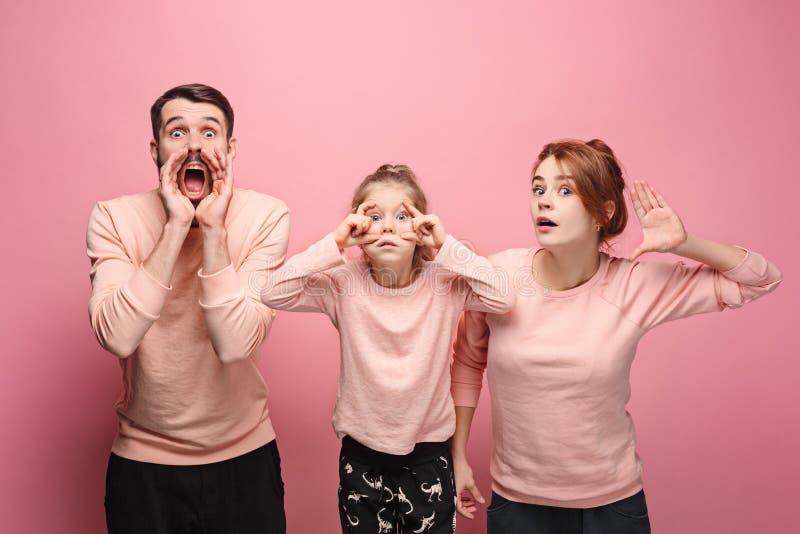 Jeune famille étonnée regardant l'appareil-photo sur le rose images stock
