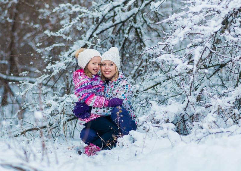 Jeune famille étreignant et riant sur la promenade neigeuse d'hiver en nature images libres de droits