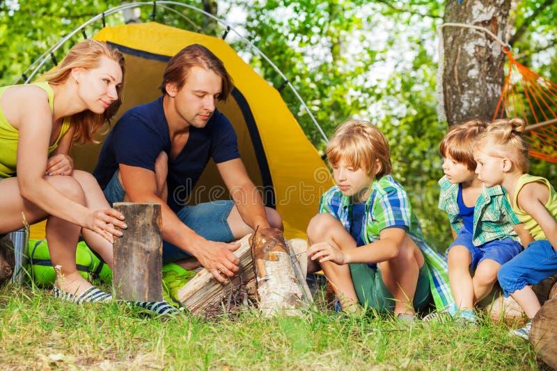 Jeune famille active faisant le feu de camp dans les bois images stock