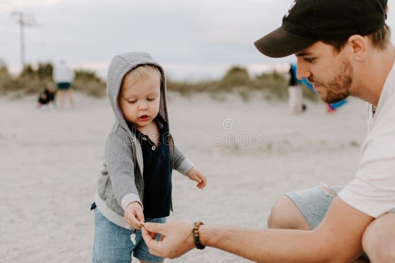 Jeune famille adorable parfaite de fils d'enfant en bas âge de père et de bébé ayant le temps d'amusement chez Sandy Beach During photos libres de droits