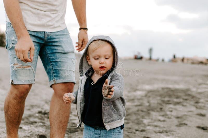 Jeune famille adorable parfaite de fils d'enfant en bas âge de père et de bébé ayant le temps d'amusement chez Sandy Beach During photos stock