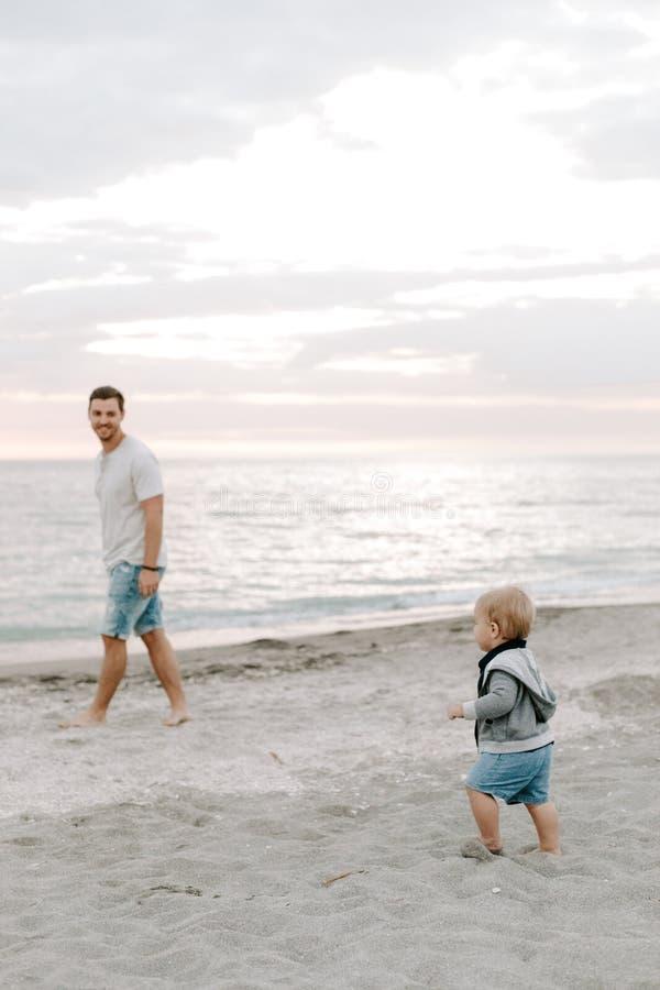Jeune famille adorable parfaite de fils d'enfant en bas âge de père et de bébé ayant le temps d'amusement chez Sandy Beach During image libre de droits