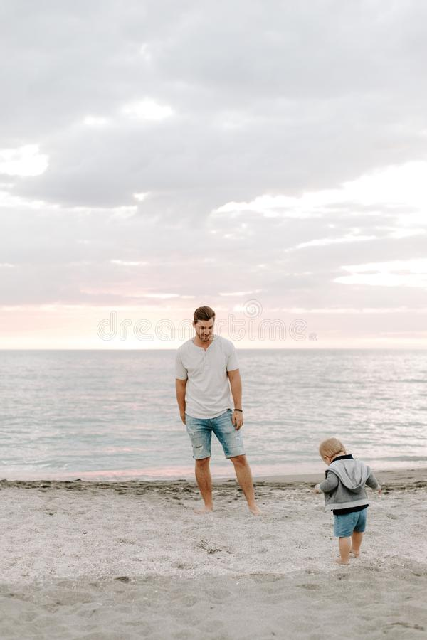 Jeune famille adorable parfaite de fils d'enfant en bas âge de père et de bébé ayant le temps d'amusement chez Sandy Beach During images libres de droits