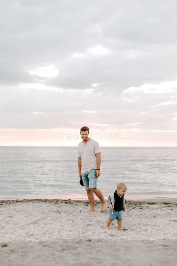 Jeune famille adorable parfaite de fils d'enfant en bas âge de père et de bébé ayant le temps d'amusement chez Sandy Beach During photo libre de droits