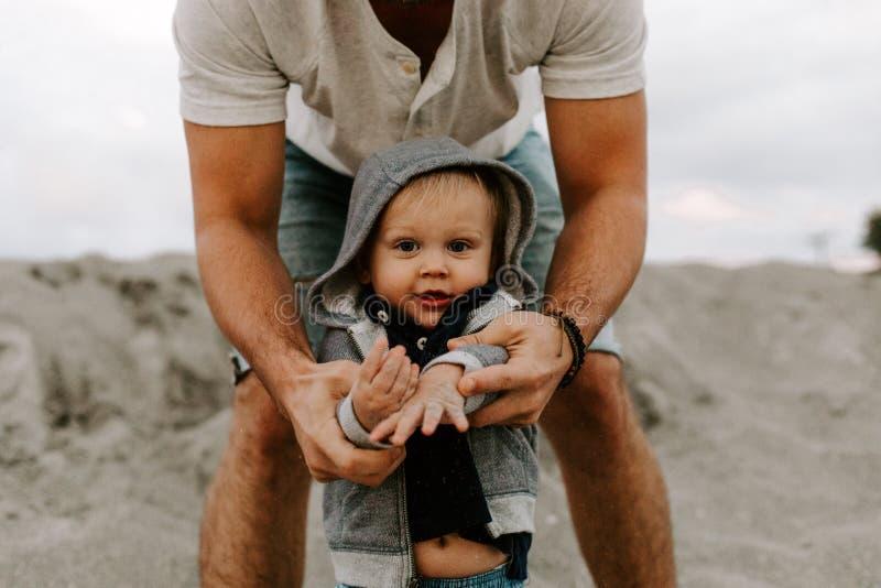 Jeune famille adorable parfaite de fils d'enfant en bas âge de père et de bébé ayant le temps d'amusement chez Sandy Beach During images stock