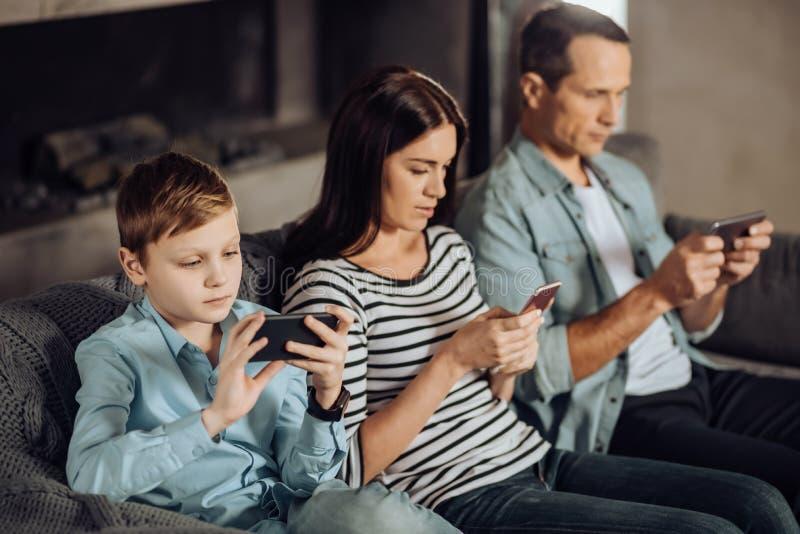 Jeune famille agréable étant dépendante à leurs téléphones photo libre de droits