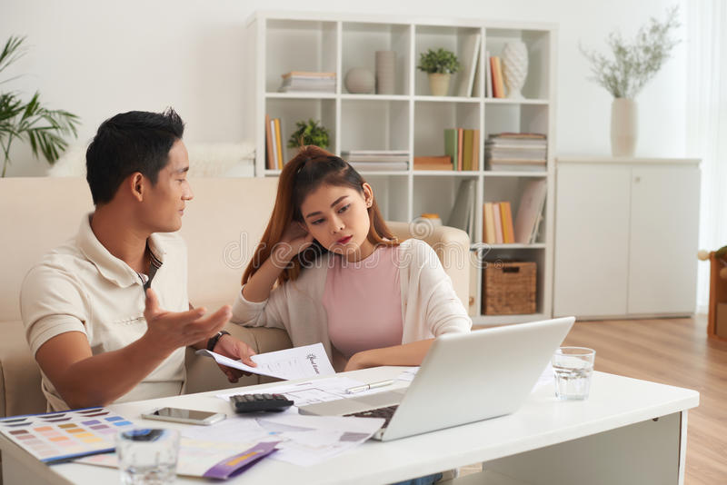 Jeune famille asiatique argumentant au sujet des finances images stock