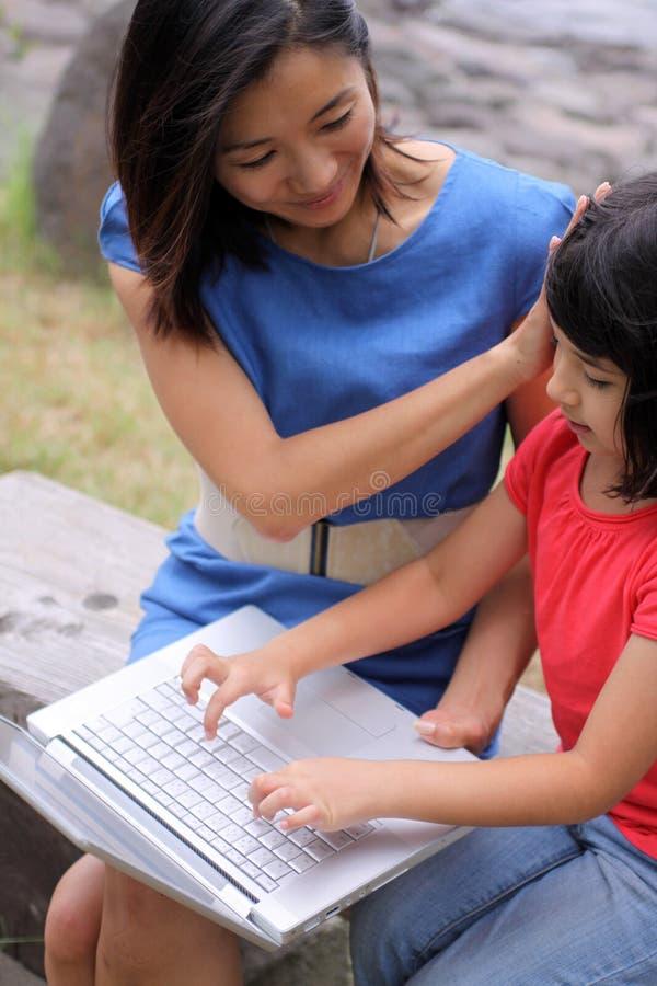 Jeune famille asiatique avec l'ordinateur portatif à l'extérieur images libres de droits