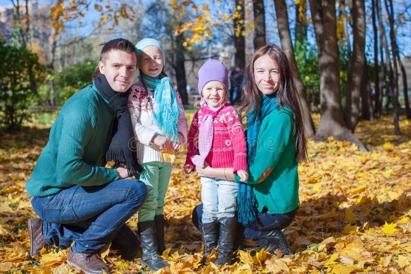 Jeune famille avec de petites filles mignonnes en parc d'automne image libre de droits