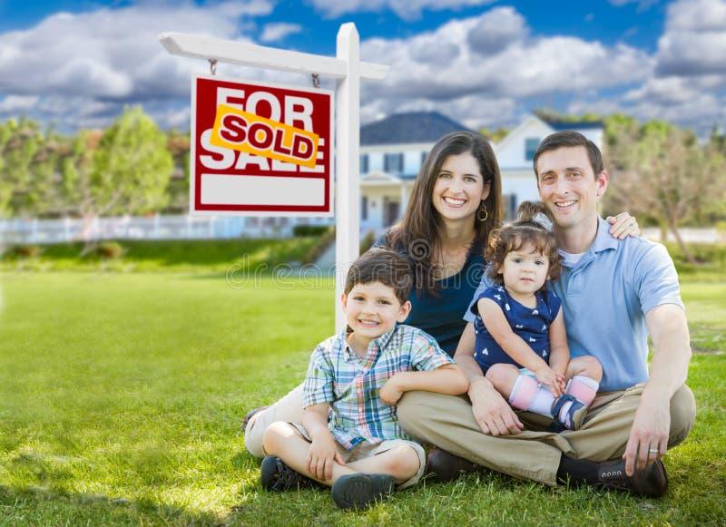 Jeune famille avec des enfants devant la maison faite sur commande et vendus pour le signe de vente photographie stock libre de droits
