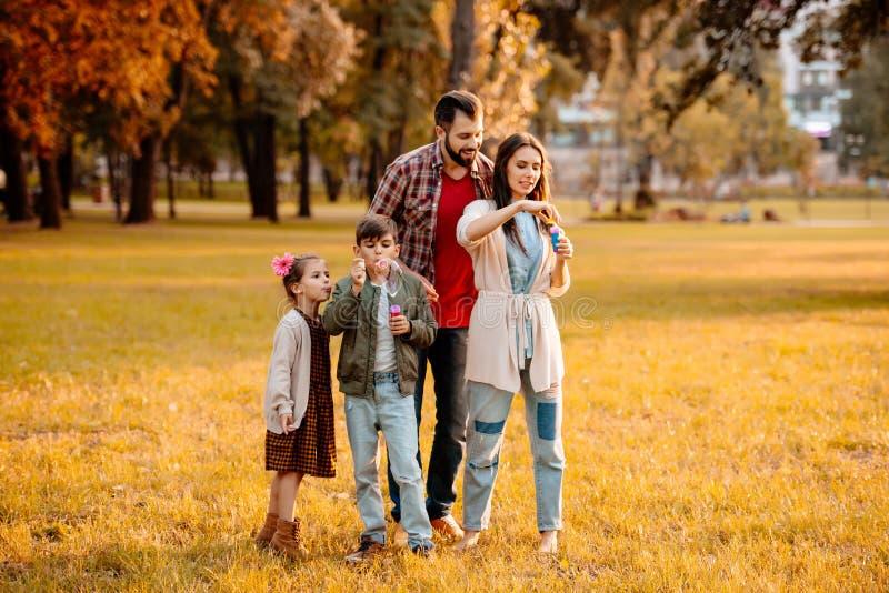 Jeune famille avec deux enfants jouant avec des bulles de savon images stock