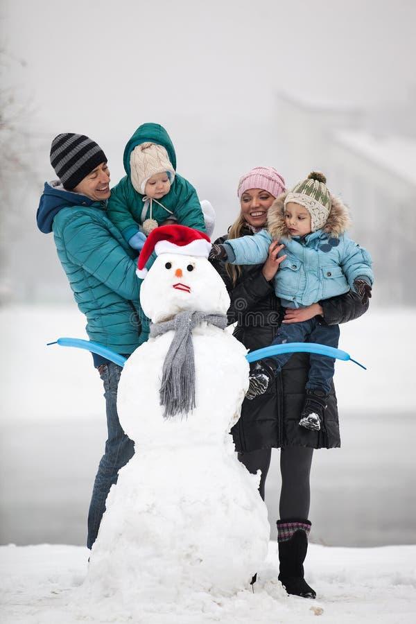 Jeune famille avec deux fils près de bonhomme de neige dehors image libre de droits
