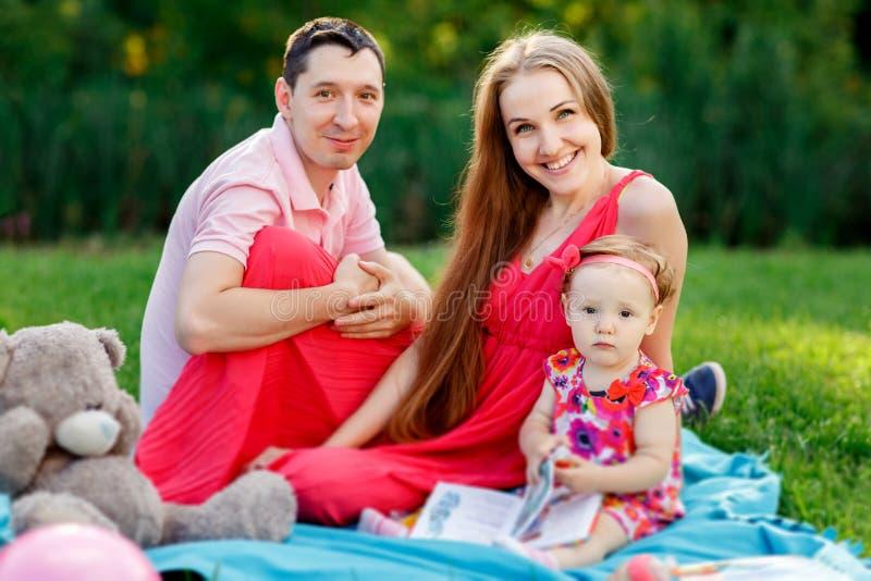 Jeune famille avec la fille et le livre se reposant sur le plaid image stock