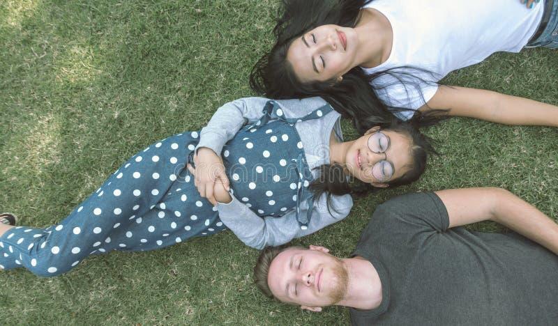 Jeune famille avec la fille s'étendant en parc sur l'herbe verte et regardant l'appareil-photo, vue supérieure photographie stock libre de droits