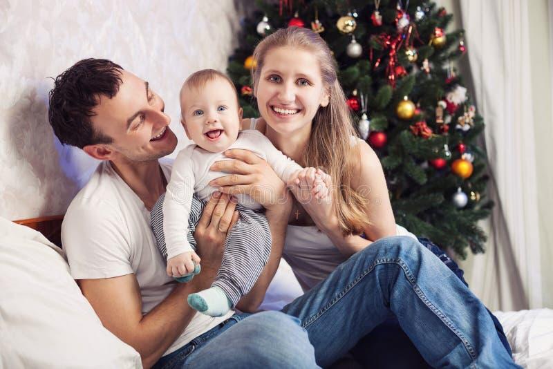 Jeune famille avec le bébé à la maison avec l'arbre de Noël photos stock