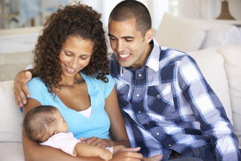 Jeune famille avec le bébé détendant sur Sofa At Home image libre de droits