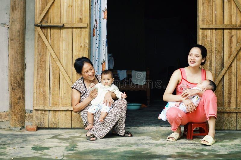 jeune famille avec les enfants et la grand-mère devant leur maison image libre de droits