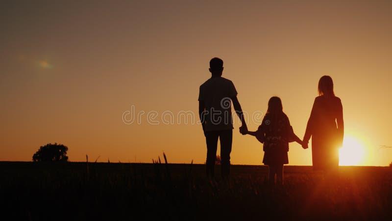 Jeune famille avec un enfant admirant le coucher du soleil dans le domaine, tenant des mains photo libre de droits