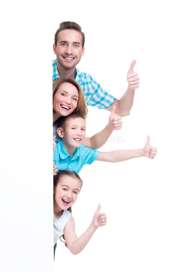 Jeune famille avec une bannière montrant les pouces- images stock